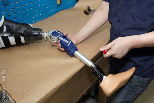 A technician adjusts a prosthetic foot.