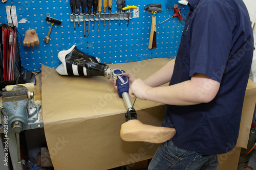 A technician adjusts a prosthetic foot.