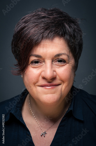 Middle age woman close up portrait on dark background.