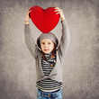 Young girl with red heart on grunge background.