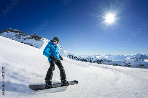 Snowboarder on piste in high mountains