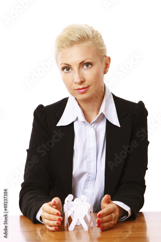 A young woman holding paper people sitting at the desk.