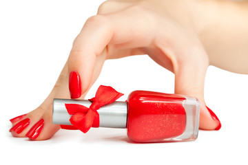 woman's hand with a bottle of red nail polish