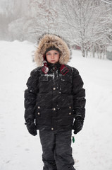 Portrait of a boy in winter clothes during snowfall