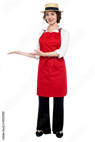 Pretty model in bakers apron presenting