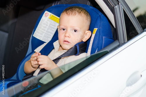 Little boy child safety seat sitting patiently back of  car