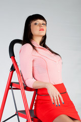 young beautiful woman is staing on the red stepladder
