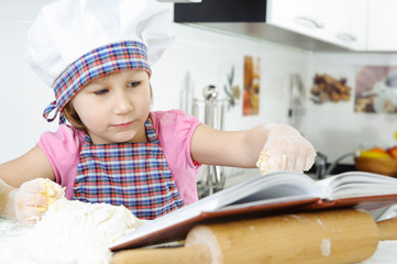 Little girl preparing cookies with cookbook