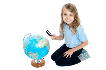 Girl watching globe through magnifying glass