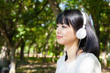 atractive asian woman listening music in the park