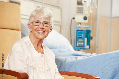 Portrait Of Senior Female Patient Seated By Hospital Bed