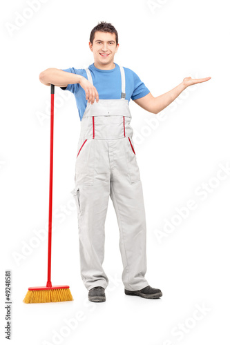 Full length portrait of a male cleaner with a broom gesturing