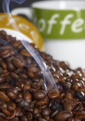 Kaffeebohnen mit Tassen und Rauch