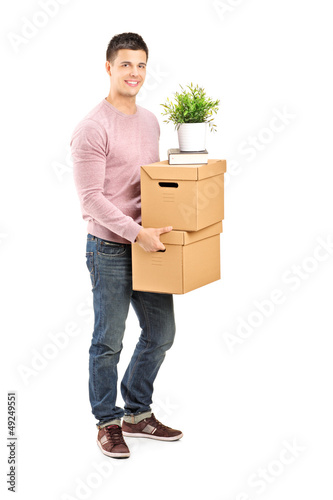 Full length portrait of a young man carrying removal boxes