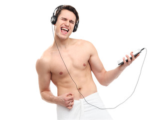 Man wrapped in towel listening to music