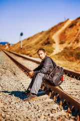 young man with backpack on railroad