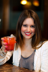 Girl drinking a cocktail in a bar