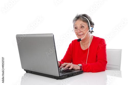 Ältere Frau mit Headset isoliert in Rot mit Computer