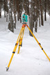Electronic tacheometer on tripod in winter forest vertical view