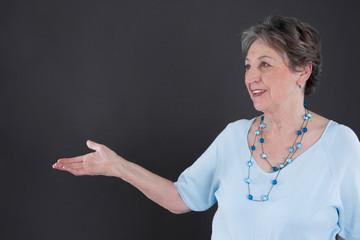 Ältere grauhaarige Dame wirbt für etwas