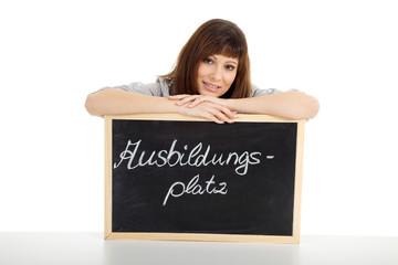 Junge Frau präsentiert freundlich Tafel für Ausbildungsplätze
