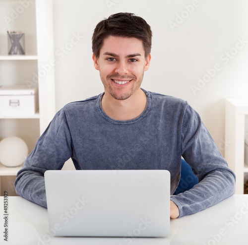 Smiling young man using a laptop
