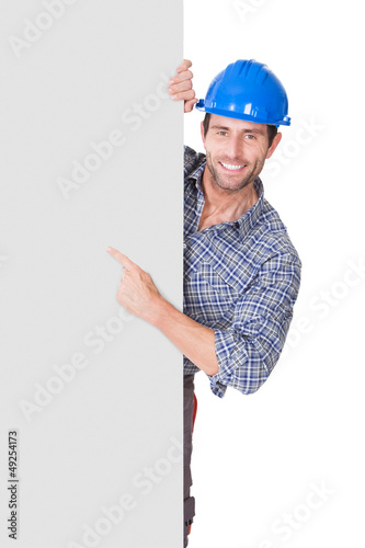Portrait of happy worker presenting empty banner