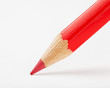 red pencil draws or writing on white paper sheet