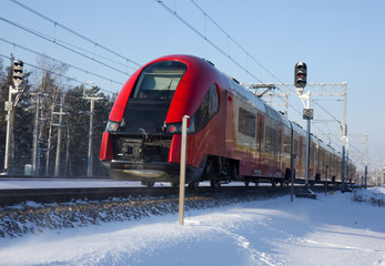 High-speed modern commuter train riding among snows