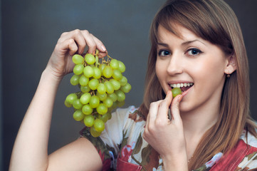 the smiling girl is eatting  grapes