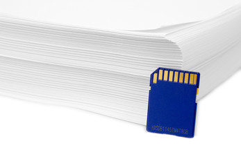 Sd memory card with a stack of printer paper. Hardcopy backup or