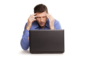 Man frustrated with his laptop computer on white backround