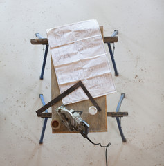 Wooden table with blueprints and  saw