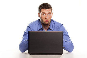 confused man on a laptop with a face gesture