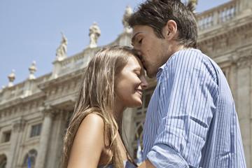 Caucasian man kissing girlfriend