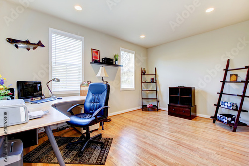 Home office with hardwood floor and simple furniture.
