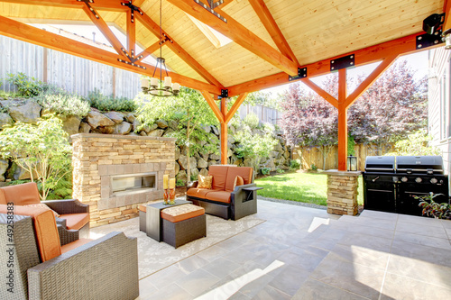 Exterior covered patio with fireplace and furniture.