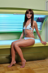 smiling girl sitting on a solarium
