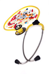 Pills and yellow stethoscope