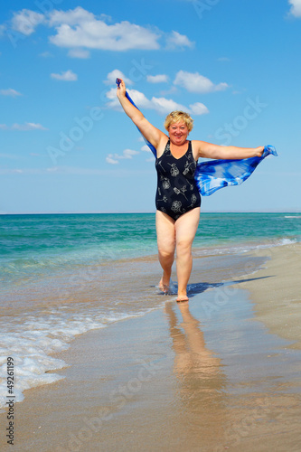 active mature woman running the beach