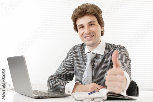 Happy young business man holding his thumbs up