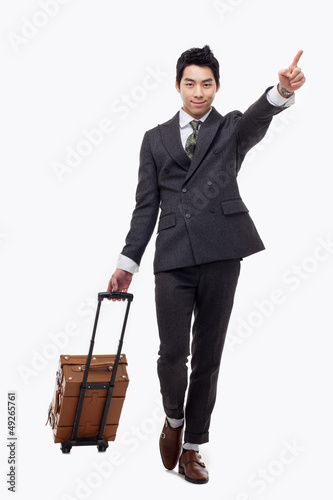 Businessman walking along pulling some travel luggage