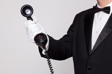Butler holding a phone handset