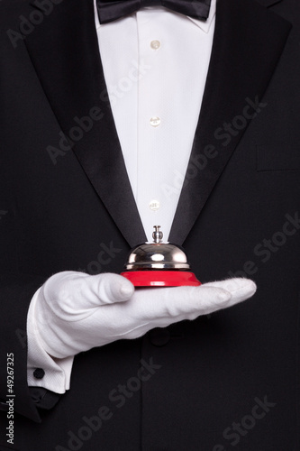 Waiter holding a service bell.