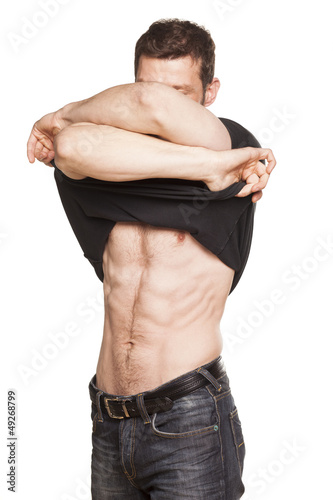 Handsome man takes off the shirt on white background