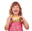 happy little girl eat big sandwich on white