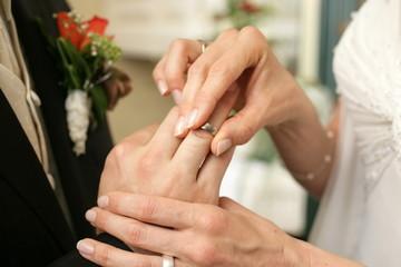 Braut streift Ihrem Braeutigam den Ehering ueber