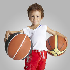 Child in basketball uniform and two balls