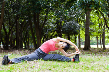 attractive asian woman stretching the park