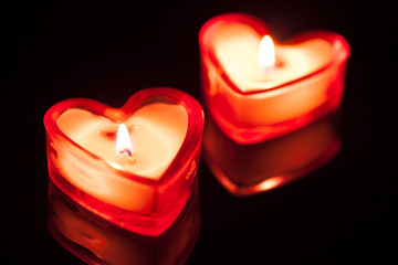 two burning candle hearts